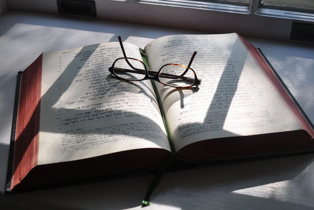 hebrew scripture and reading glasses
